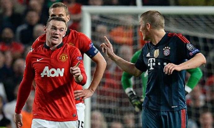 Bayern's Bastian Schweinsteiger fumes at Manchester United's Wayne Rooney after being sent off